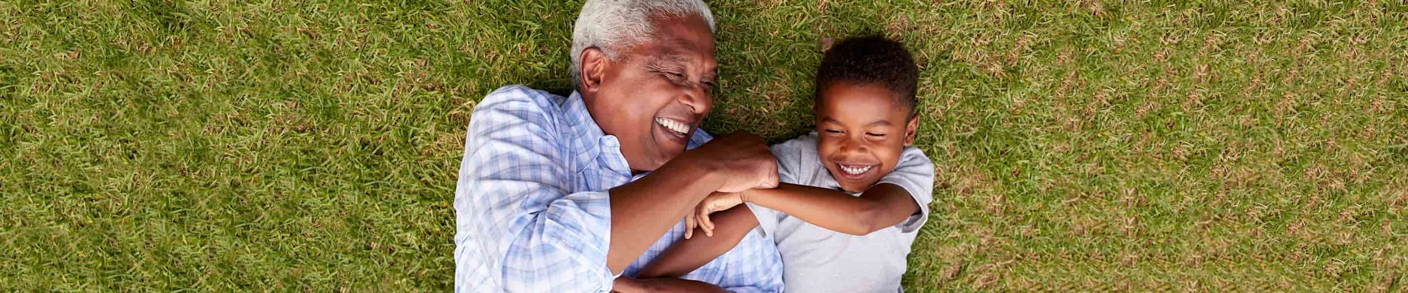 Grandfather and grandson laughing while laying on the grass.
