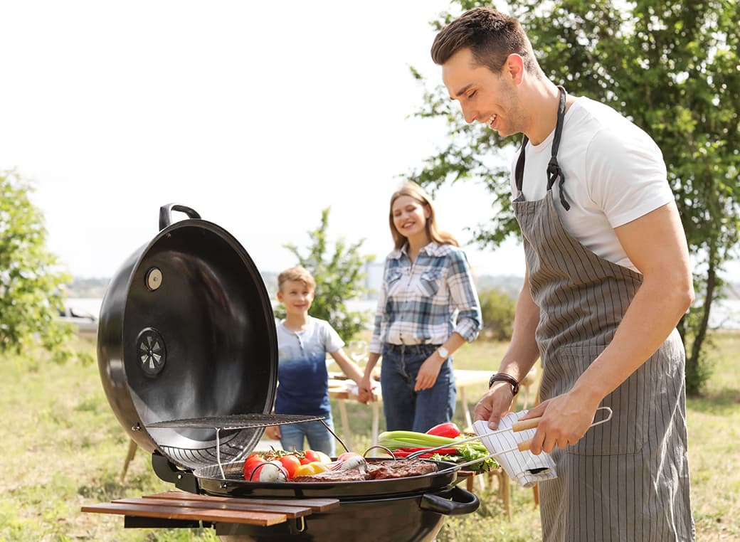 Happy family having a barbecue with grill outdoors.